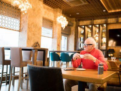 Satisfied senior man drinking freshly brewed coffee